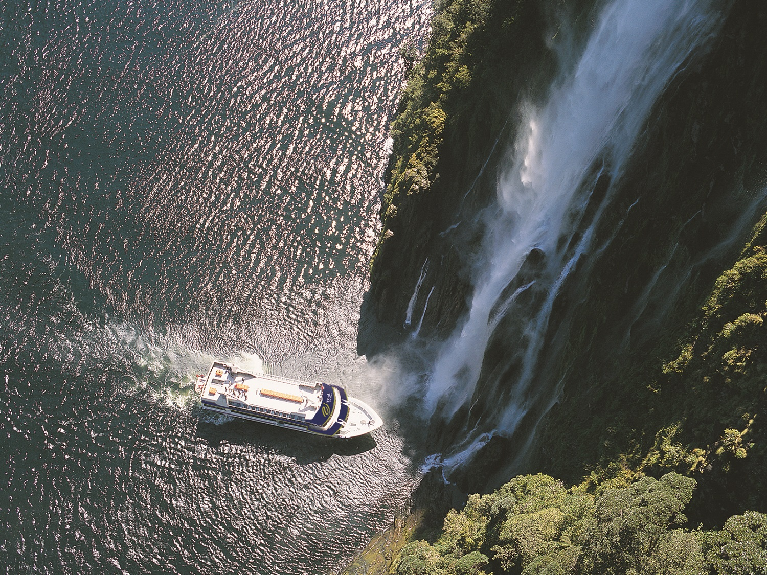 A day trip boat points its bow into Stirling Falls.