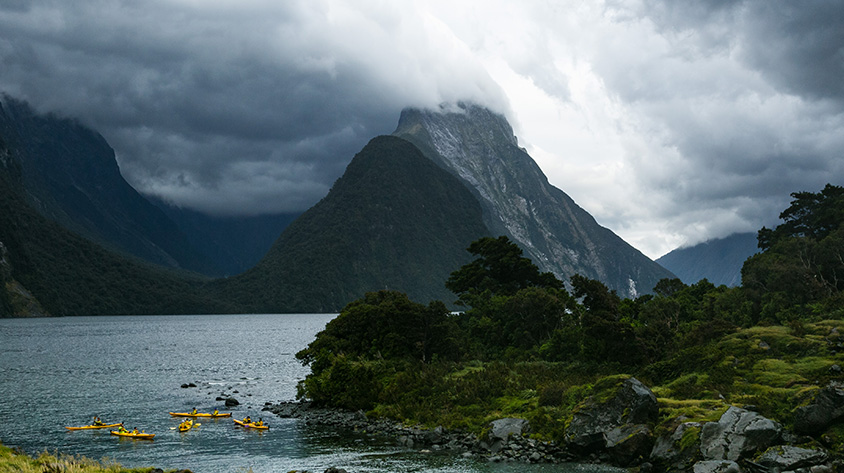 Kayaks in Milford sound on a cloudy day