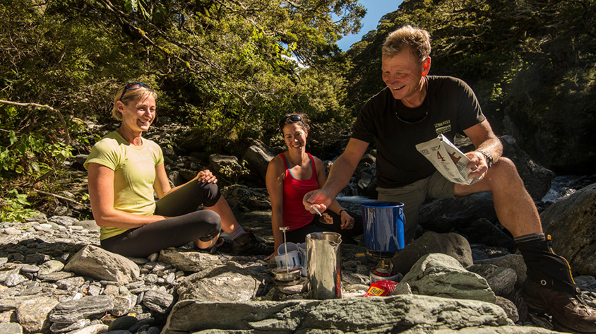 New Zealand Great Walk guide making coffee on a stony creek bed
