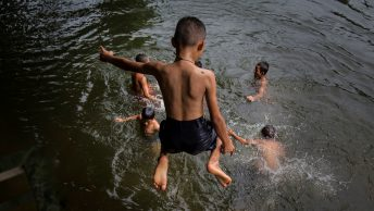 children play swim river