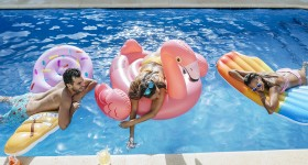 Spain, Andalusia, cadiz, El Puerto de Santa Maria, Friends in pool mounted on ice cream and flamingo floats.