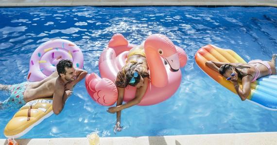 Spain, Andalusia, cadiz, El Puerto de Santa Maria, Friends in pool mounted on ice cream and flamingo floats.