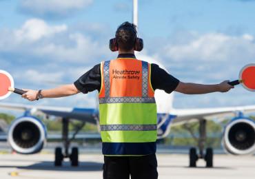 Heathrow, airfield, airfield ops marshaller guiding aircraft on apron, Sep 2018.